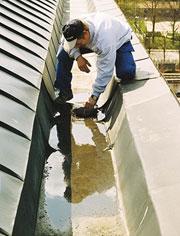 Bild 12:38. Alla ränndalar – inklusive brunnar – tillhör takets viktigaste detaljer och måste noga kontrolleras och underhållas. Vintertid krävs ibland snöskottning. Den ska naturligtvis utföras på ett sådant sätt att taktäckningen inte skadas. Foto: Torbjörn Osterling.