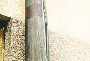 Bild 12:42. Längdskarven ska vid vattenabsorberande fasadmaterial alltid vändas ut från fasaden för att undvika skador på putsen vid en eventuell issprängning. Bilden visar en fals som sprängts sönder av is. Rördelen bör bytas. Foto: Torbjörn Osterling.