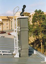 Bild 12:51. Kontrollera infästning av och eventuella korrosionsangrepp på beslag med mera på skorstenar. Kontrollera även eventuella uppstignings-anordningar. Foto: Torbjörn Osterling.