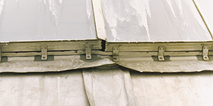Bild 8:11. Här finns en rörelsefog i stålstommen under glaslanterninerna. Rörelsefogen har inte fullföljts i glaslanterninen och täckbeslaget mellan olika element i lanterninen. Glipor har uppstått. Skadorna hade kunnat undvikas genom att rörelsefogen i stommen dragits igenom lanterninen och att lanternindelarna på ömse sidor skiljts från varandra. Foto: Torbjörn Osterling.