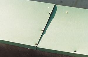 Bild 8:3. Stum överlappsskarv på ett beslag. Vissa nitar har skjuvats av medan andra håller på att lossna. När denna typ av skarvning används är det nödvändigt att lägga in rörelsefogar med jämna mellanrum. En sådan kan utföras som ett förstorat tätat överlapp med omslag. Foto: Torbjörn Osterling.