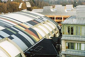 Bild 2:2. Plåt som tak- och fasadmaterial ger stora möjligheter till varierad utformning. I förgrunden ett tak med färgbelagd förzinkad stålplåt och i bakgrunden sömsvetsad rostfri stålplåt som både fasadbeklädnad och taktäckning. Foto: Torbjörn Osterling.
