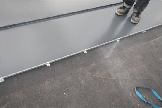 Bild 6:11. Under plan plåt används byggpapp dels som ett skydd under byggtiden dels som ett senare kondensskydd. Skarvar på papp ska snedskäras för att undvika att vatten ska ledas in i överlappen. Foto: Torbjörn Osterling.