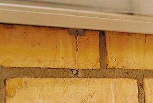 Bild 10:15 Infästning av fönsterbleck med trådklammer före putsning av fasaden. Trådklammer ska utföras som figur 10:51.  Foto: Torbjörn Osterling