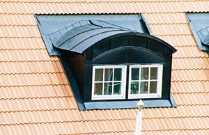 Bild 12:50. Vid takkupor och liknande kontrolleras anslutningar mellan tak och väggytor samt infästning och täthet vid galler, fönster och dylikt. Foto: Torbjörn Osterling.