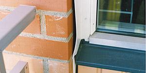 Bild 8:12. Rörelserna i stommen respektive skalmuren har medfört att smyglisten deformerats. Smyglisten har här monterats dels i karmen dels i skalmuren. Fönstret är monterat i den bakomliggande betongstommen som rör sig mindre än skalmuren. Foto: Torbjörn Osterling.