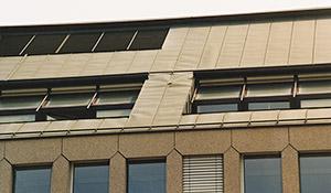 Bild 8:7. Långa och korta band har falsats samman med en dubbel ståndfals. Vid hörnen till fönsteromfattningarna medför rörelserna i de längre plåtarna att det uppstår dragningar i plåten. Så småningom kan detta leda till att det uppstår sprickor i de längre plåtarna. I detta fall borde en rörelsefog ha placerats i överkant på fönsteromfattningarna och mellan de olika fönsterdelarna. Foto: Torbjörn Osterling.